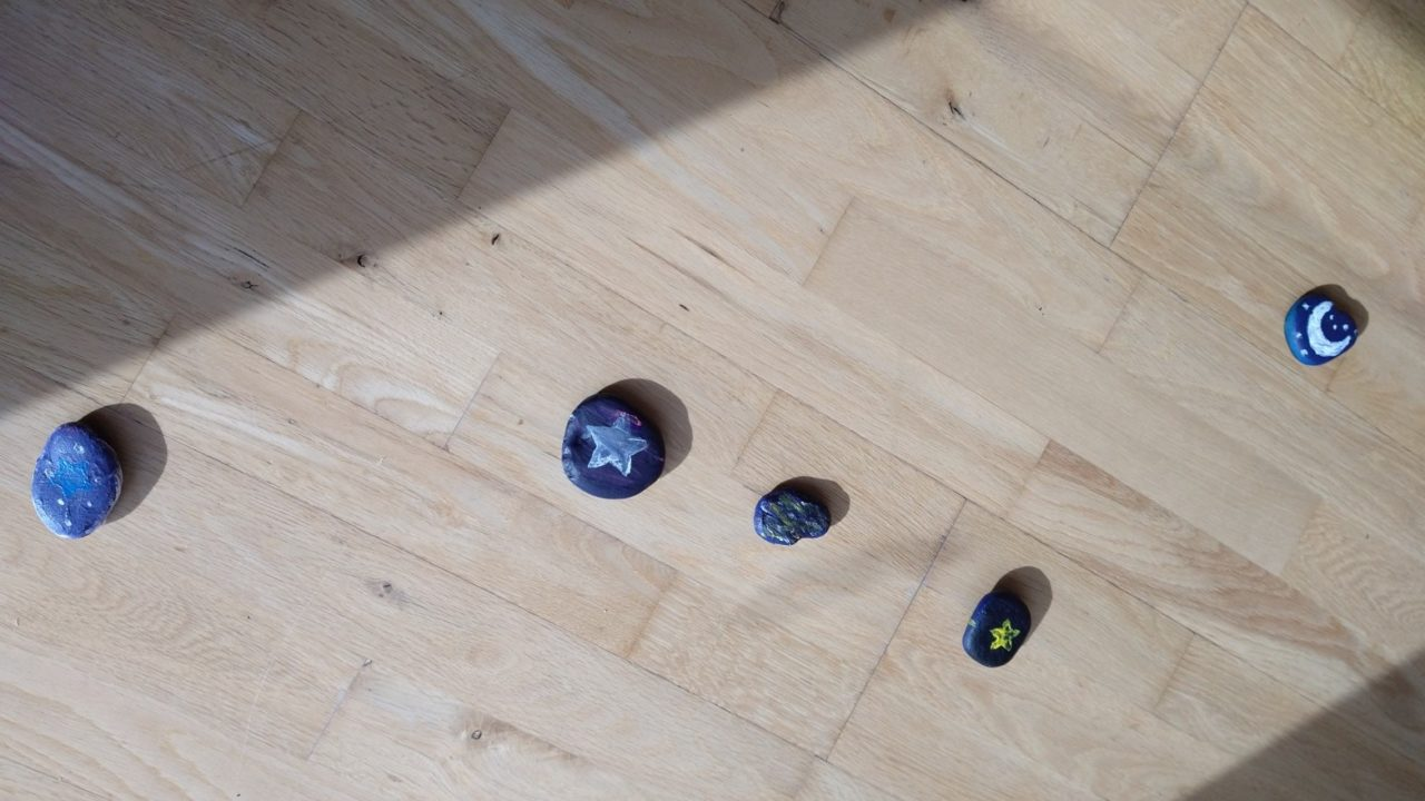a photograph of stones painted with images of the night sky