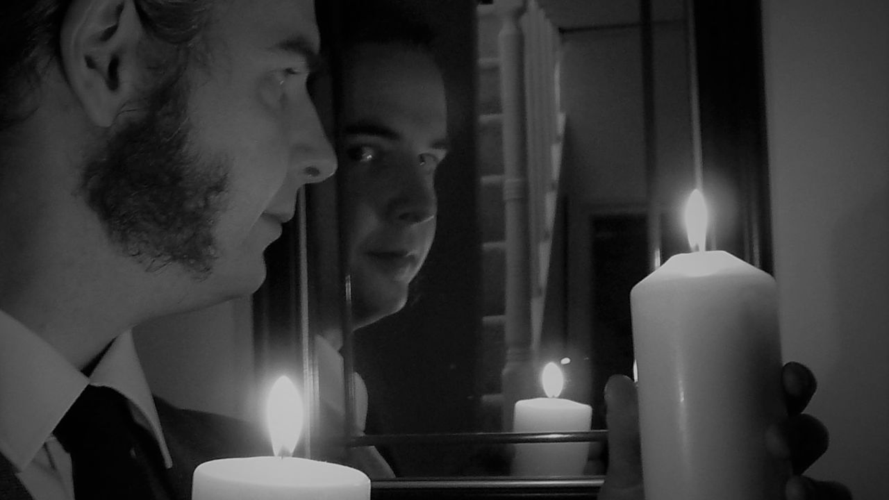 Tim Ralphs with 2 candles looking into a mirror