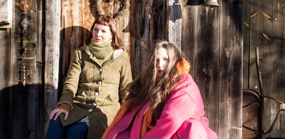 Heidi & Kristin outside a wooden door in a forest in Norway